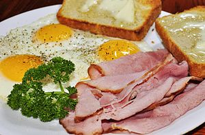 "Fried egg - Ham and eggs served with fried eggs prepared ""sunny side up"""