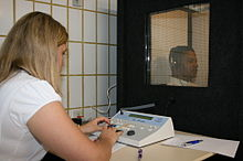 a female medical professional is seated in front of a special sound-proof booth with a glass window, controlling diagnostic test equipment. Inside the booth a middle aged man can be seen wearing headphones and is looking straight ahead of himself, not at the audiologist, and appears to be concentrating on hearing something