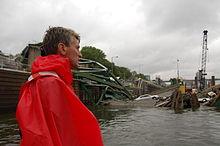 RT Rybak in einem roten Poncho mit Blick auf die eingestürzte Brücke im Wasser