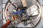 ISS-59 Anne McClain works inside the crew lock of the Quest airlock.jpg