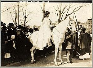 Inez Boissevain, wearing white cape, seated on...
