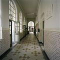 Interieur, overzicht van een gang met een lambrisering van geglazuurde tegels en een tegelvloer - 's-Gravenhage - 20387483 - RCE.jpg