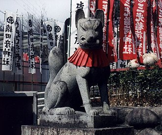 Inari Ōkami - Statue of a kitsune adorned with a red votive bib in a shrine at Inuyama Castle.  Many castles in Japan contain Inari shrines.
