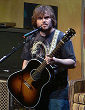 A photograph of Jack Black, in casual clothes, holding an acoustic guitar while on stage.