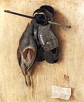 A dead bird and two leather gloves hanging on a wall