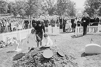 John F. Kennedy Eternal Flame - Mrs. Kennedy and her children visit the temporary grave of President Kennedy on May 29, 1964 (the President's birthday). The evergreen boughs cover the base of the temporary Eternal Flame at the head of the grave vault. Note the military hats on the evergreen boughs.