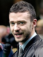 Head and shoulders of Justin Timberlake, wearing a light blue shirt, ablack and white tie and a black jacket, speaking into a microphone
