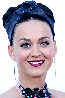 Katy Perry looking straight and smiling.