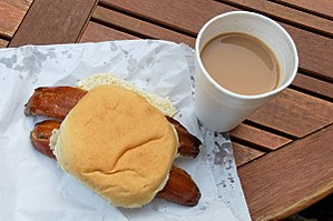 "Craster kipper - Two Craster kipper fillets served in a white bap with a cup of tea — the famed ""kipper tea"""