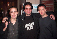 Three dark-haired men wearing dark clothing. The man on the left is wearing a checkered shirt with a rain jacket. The man in the middle is wearing a printed tee with a rain jacket. The man on the right is wearing a black sweater.