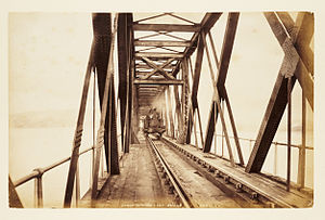 Sepia colourted photograph of the section of the first Tay Bridge before its collapse. A steam train is crossing the bridge.