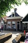 foto van Eenvoudige woning onder zadeldak met voorschild met forse schoorsteen met bord en dakkapel met bloklijsten