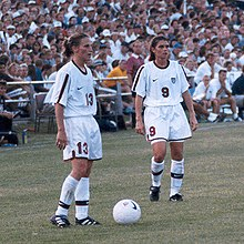 Soccer players Kristine Lilly and Mia Hamm standing over a ball while preparing to take a free kick.