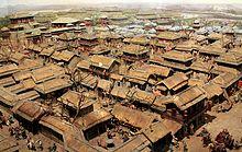 Photographie d'une ville. Constructions basses à l'avant, plus élevées à l'arrière. Toits de tuiles couvertes de chaume.