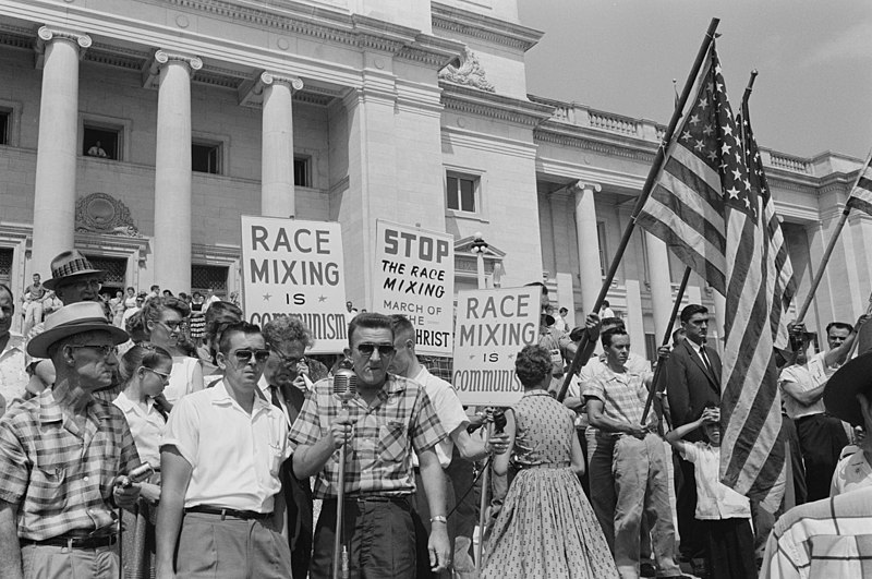 Little Rock, 1959. Rally at state capitol, protesting the integration of Central High School. Protesters carry US flags and signs reading