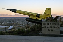 The black and yellow missile sits on display overlooking desert and mountains of New Mexico