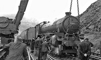 Crane (rail) - A derailed steam locomotive being lifted back onto the tracks by a rail mounted crane in 1951