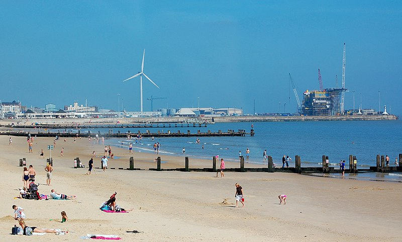 Lowestoft seafront showing the beach and the outer harbour with wind turbine and gas rig.