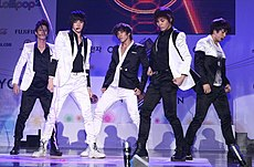 Five men with bowl haircuts and eyeliner wearing close-fitting, shiny suits--some black with white embellishment, others white with black embellishment.