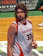 A basketball player, wearing a white jersey with the word «AKASVAYU» and the number 33 on the front, stands on a basketball court.