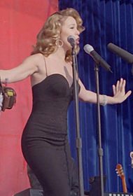 A woman in a black ensemble, performing a song at the filming of a music video.