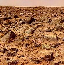 Zdjęcie. Brunatna pustynia pokryta licznymi skałami.
