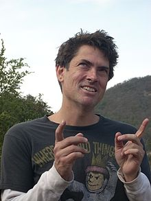 Smiling man outdoors, holding up both index fingers