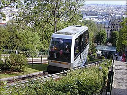 Photograph looking down the outlier (French: butte) of Montmartre showing the back and roof of a cabin. A panorama of Paris below fills the background.