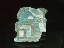 Fragmentary relief of green glaze showing a woman seated.