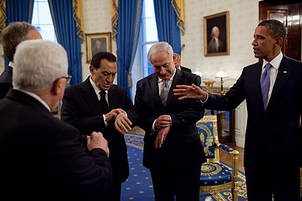 During 2010 Middle East negotiations in the United States, Hosni Mubarak and Benjamin Netanyahu check their watches to see if the Sun has set. Netanyahu and Mubarak checking their watches.jpg
