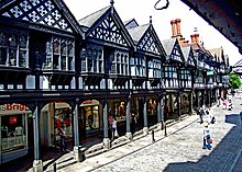 A street containing a range of two-storey shops on the left seen from a slightly elevated position.  The lower storey contains modern shop fronts behind an arcade; the upper storey is timber-framed and contains a variety of windows and decorated gables.