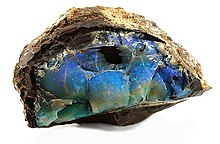 A blue-green section of opal encased inside a light brown rock