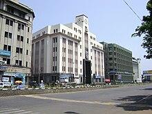 een gebouw met meerdere verdiepingen, met de weg op de voorgrond