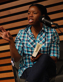 A woman is sitting in a chair and holding a book. She is speaking into a microphone to an unseen audience.