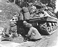 Photograph of a Tank Destroyer Crew Playing Craps While Awaiting Removal of a Road Block - NARA - 6927819.jpg