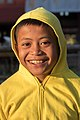 Portrait in sunshine at golden hour of a smiling boy wearing a yellow sweater with hood pulled up in Laos.jpg
