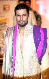 Hooda walking the ramp wearing a golden sherwani.
