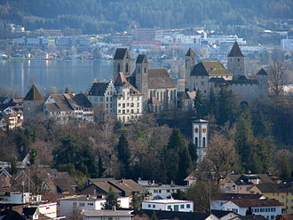 Stadtmuseum Rapperswil-Jona - Herrenberg hill and town walls of Rapperswil: Rapperswil Castle to the right, Liebfrauenkapelle, ''Stadtpfarrkirche'', Herrenberg primary school and Stadtmuseum to the left, as seen from Kempraten, Seedamm and Hurden in the background
