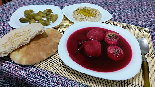 A bowl of kubbeh adom, or red kubbeh in a beet broth