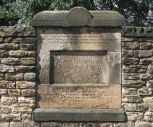 The Bridgeness Slab - The weather-worn previous copy of the tablet installed in response to the terms of the donation which contained the text but not the side panels. It reads:'NEAR THIS SPOT ON 29TH APRIL 1868, A LEGIONARY TABLET WAS DISCOVERED, xxxx AT EACH SIDE GROUPS OF FIGURES IN RELIEF xxxx THE CENTRE THE FOLLOWING INSCRIPTION.'