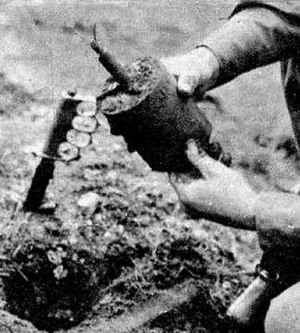 S-mine - An American paratrooper demonstrates the process of removing a live S-mine. On the left is a Mark I knife