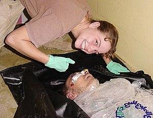 Sabrina Harman posing over the body of Manadel...
