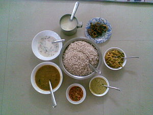 Cuisine of Kerala - Sadya items ready to be served, Clockwise from top Paayasam, Bittergourd thoran, aviyal, Kaalan, Lime Pickle, Sambar, Buttermilk with Boiled rice in center