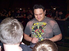 A dark-skinned adult male wearing a multi-colored T-shirt signing an autograph