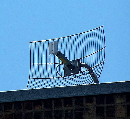 Wire grid-type parabolic antenna used for MMDS data link at a frequency of 2.5-2.7 GHz. It is fed by a vertical dipole under the small aluminum reflector on the boom. It radiates vertically polarized microwaves. Screen dish antenna.jpg
