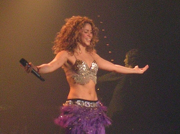 An image of a performing woman with long brown hair. She is wearing a sleeveless gold-sequined top and a purple-feathered skirt. Her arms are extended outwards, and she holds a microphone in her right hand.