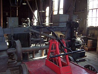 Railtown 1897 State Historic Park - Sierra Railway machine shop. Hand car and wheel press are in foreground. Shaper and engine lathes in background. Machines are driven by an overhead, flat-belt line shaft.