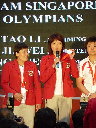 Li Jiawei - Li speaking during a ceremony on 25 August 2008 welcoming Team Singapore home from the 2008 Summer Olympics, flanked by Wang Yuegu and Feng Tianwei