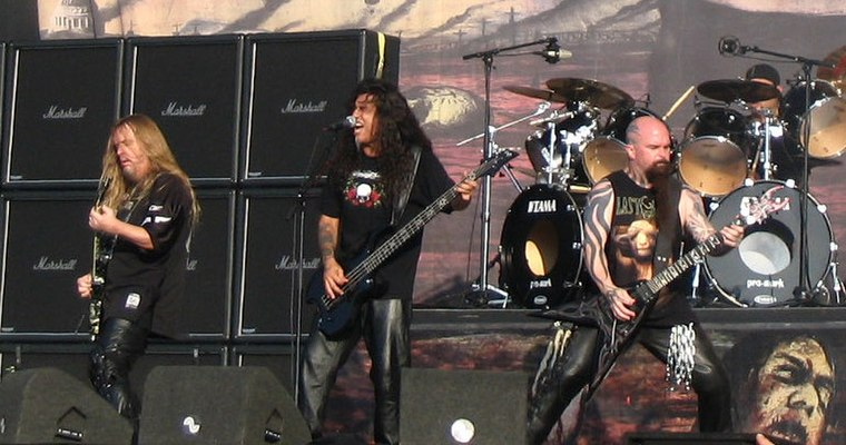 Three men on a stage, all holding guitars. All three are wearing black clothing, and audio equipment can be seen both in front of and behind them.