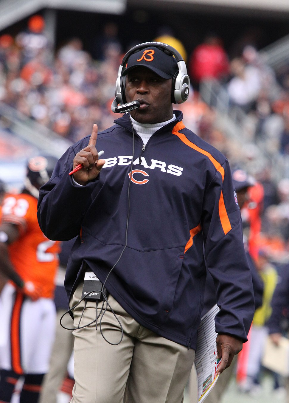 Photograph of Smith wearing a Bears pullover jacket, Bears baseball cap and headset on the Bears sideline
